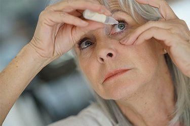 Woman applying eyedrops