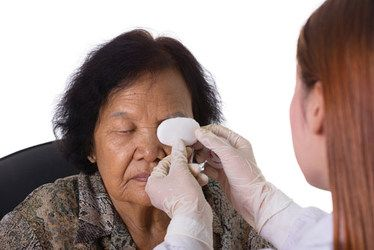 Woman having gauze placed over her eye