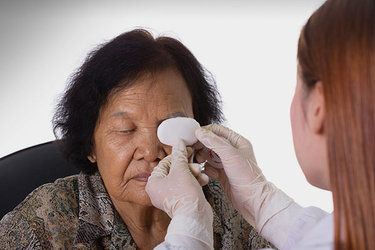 Woman holding eye patch over female patient's eye