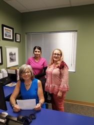 Three New Mexico Smile Center staff members standing in office.