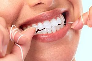 A close up of a woman flossing