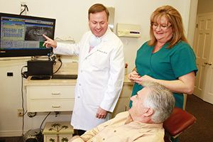 A dentist and hygienist show a patient his images on a screen.