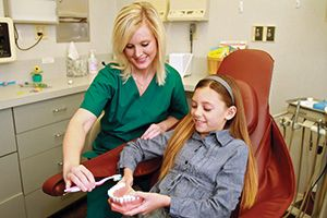 A dental hygienist wearing green scrubs shows a young child a model of a mouth.
