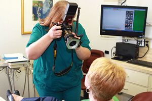 A hygienist in green scrubs taking a digital photo of a patient.