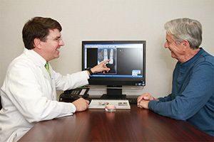 A doctor showing an older patient an X-ray of dental implants.