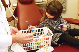 A young child in the treatment chair picking a toy from a basket.
