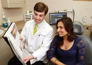 Dr. Ship showing a patient a gallery of smiles.