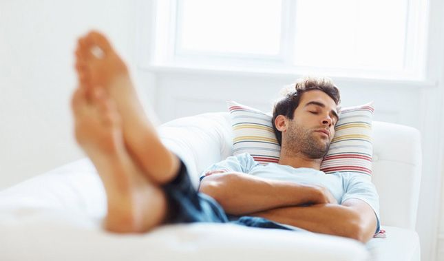 A man sleeping on a couch.