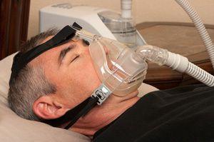 A man wearing a CPAP machine while sleeping.