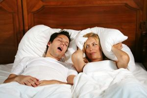 A man snoring while his partner covers her ears with a pillow.