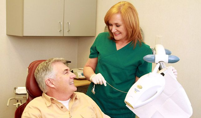 A hygienist smiling at a male patient in the dentist's chair.