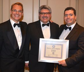 Dr. Max Teja wearing a tux and standing in between two other men while receiving a certification