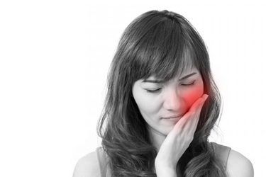 woman in pain holding the side of her face