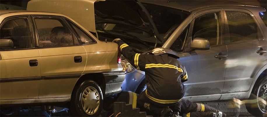 Emergency technicians examining a car accident